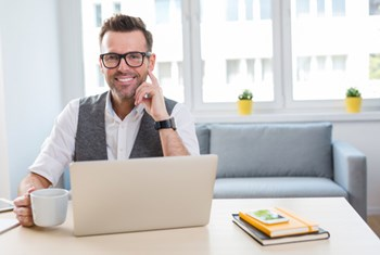 Man smiling sitting at desk working from home with laptop and cup of coffee
